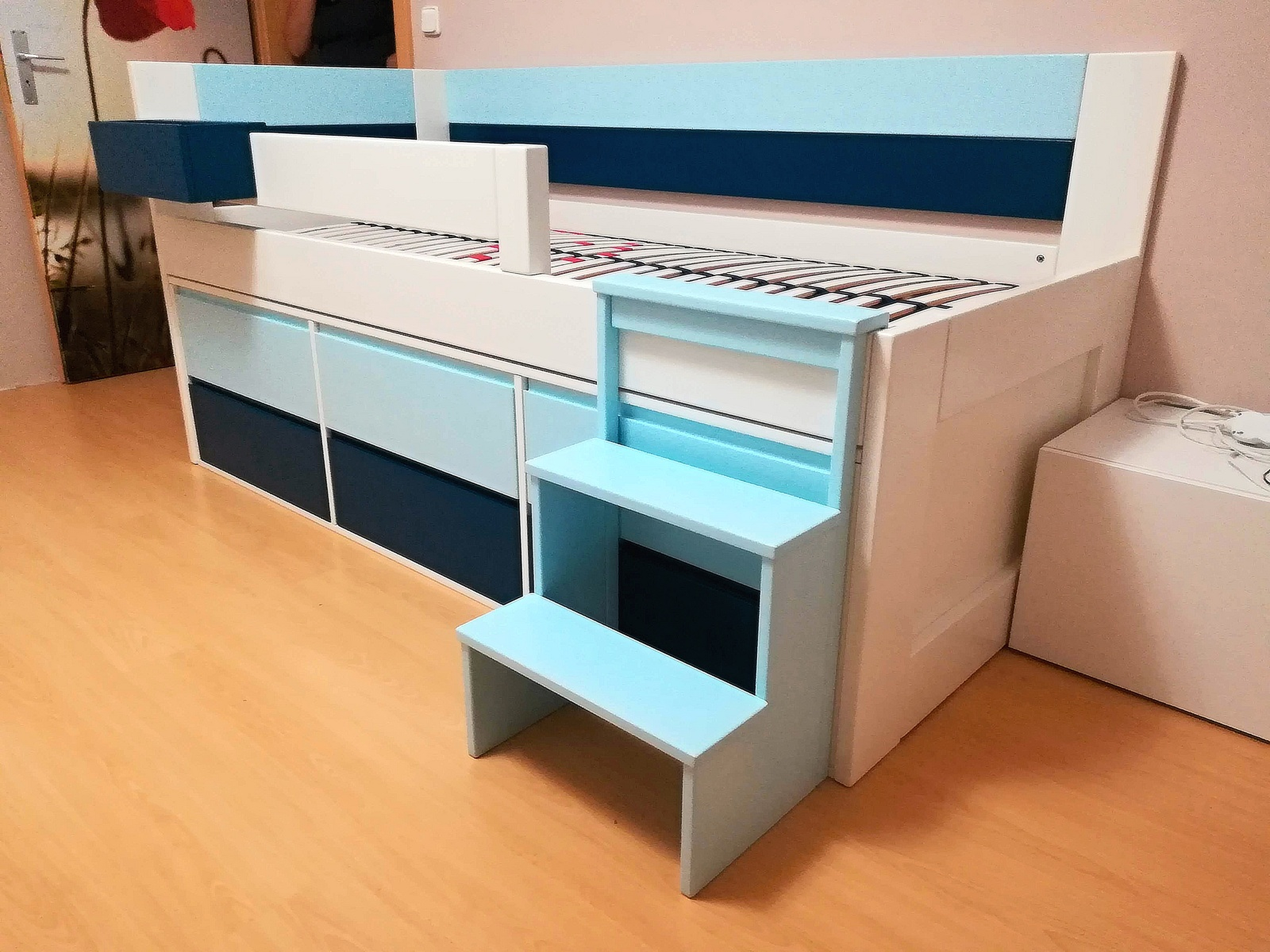 rohová postel v pastelových barvách se zásuvkami